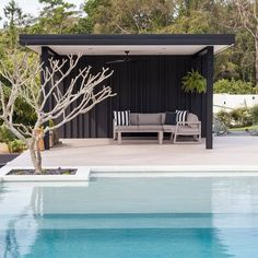 a minimalist black pool cabana with striped pillows on a single upholstered sofa. - a minimalist black pool cabana with striped pillows on a single upholstered sofa for those who dont - Backyard Cabana, Pool Gazebo, Outdoor Cabana, Outdoor Pavilion, Pool Cabana, Backyard Pool Designs, Outdoor Pool, Small Pool Houses, Modern Pool House