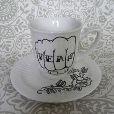 Cup and saucer set with Tea tattoo. i need this!