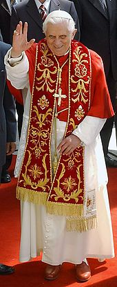 Pope Benedict XVI in choir dress with the red summer papal mozzetta, embroidered red stole, and the red papal shoes.