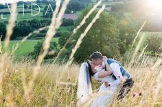 Buckland hall grounds bride and groom embrace in the meadow at sunset
