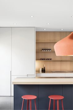 Blue lower cabinets with open shelves and peach hanging light Photography: Antoine Fortin