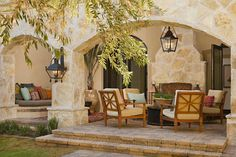 Everything is this picture is gorgeous. The architecture seems to be old Spanish style, love the lamps and the furniture, arched entryways and the furniture. Would love a porch like this!