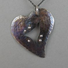 This battered and scraped up heart has a gaping rend through the middle, but sports a beautiful iridescent color play patina and high polish rivets. Metal Clay Jewelry, Metal Necklaces, Leather Jewelry, Heart Jewelry, Jewelry Art, Jewellery, Ceramic Necklace, Heart Pendant Necklace, Artisan Jewelry