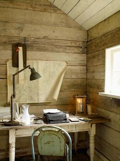 Quintessential social-phobic writer's hut: rusting chair, vintage typewriter, anglepoise lamp, map on the wall.  Utterly perfect.
