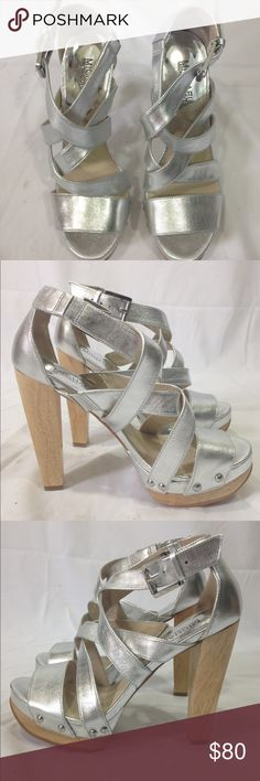 Michael Khors Silver platform sandals shoes 7 Upper: Patent Leather. Color: Silver Chunky Wood 3.                                                     platform and 4 mm heel. Ankle strap with adjustable buckle closure. Crisscross straps at open toe. Leather lining and insole. Man-made outsole. Condition: New, in original box. The elastic strap of one of the shoes is slighly longer not visible at all.  Retail: $189.00 MICHAEL Michael Kors Shoes Platforms