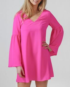 5ad7fc7da752 Shine bright in this fuchsia colored bell-sleeve mini dress. With criss  cross detail