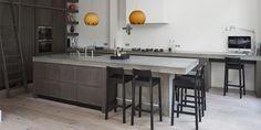"""Massief eikenhouten woonkeuken met betonnen werkblad Deze op maat gemaakte keuken is geplaatst in een voormalig koetshuis in Den Haag. De gehele benedenverdieping is een zeer plezierige woonkeuken geworden. In deze ruimte wordt gekookt, gegeten, gewerkt en zeer zeker ook ontspannen. """"De gehele benedenverdieping is een plezierige woonkeuken geworden."""" Een moderne keuken met hoge kasten De moderne keuken is gemaakt van massief eikenhout en heeft een bruine beits gekregen. Ondanks het hoge…"""