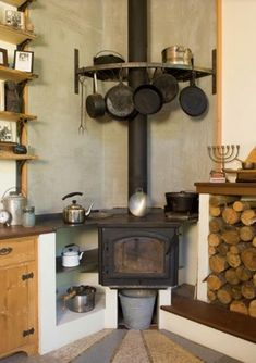 """Pemberton came up with a design that turned the stove into a cooktop. The stove is raised so the top is at countertop height, and it has a big sheet of metal on top, creating varying temperatures for cooking. """"Put it right above the stove and you can boil Wood Stove Cooking, Kitchen Stove, New Kitchen, Küchen Design, House Design, Wood Rack, Rustic Kitchen Decor, Rustic Decor, Stove Fireplace"""