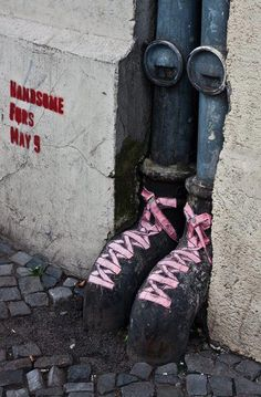 Pink laces on black drain pipe shoes