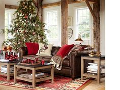 A mix of rich reds and browns, plus a range of textures makes this room the family favorite. Leather furniture offers a bit of casual shine. The wood and stone occasional tables give a strong edge to the softness of the sofa, pillows, and glimmering ornaments and glassware. A leopard-print throw and a pillow printed with a dog festooned in holiday garb are as visually refreshing as the twinkling Christmas tree.
