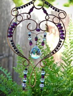 e16864e79253 It is a Sun Catcher for hanging in window. Has copper wire bent into a  heart shape. Beads wrap frame and crystal is suspended in center