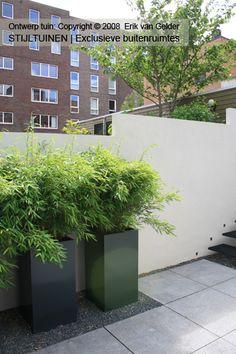 Mooie planten in hoge zwarte bakken in grind tussen tegels