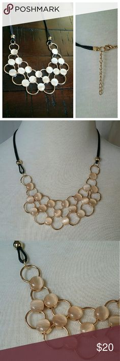 Gold tone linked statement necklace. Beige Pearl-tone round stones interlinked with round gold rings to form a gorgeous necklace. The chain is sustained with double black rope chain that is fastened with a lobster claw in the back. Adjustable to different lengths.  Gorgeous with an outfit for the office or a weekend getaway sundress. monarch Jewelry Necklaces