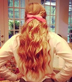 curly hair with bright pink bow.