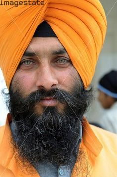 Portrait of a beautiful Sikh man (he is one of the guards in the entrance to the holy Golden temple) in Amritsar, India
