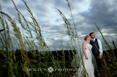 Bride and Groom in field at sunset on their wedding day at Bristol Harbour Resort in the Finger Lakes. Photo by top NY wedding Photographer Heather McKay.