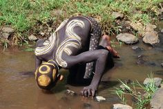 Africa |  People.  Surma man having a drink of water down by the riverside.