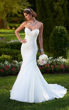 Look through sweetheart neckline strapless fit-and-flare wedding gowns featuring an asymmetrical ruched bodice and skirt with a full skirt just below the hip.