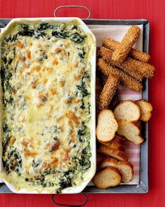 Spinach Dip  2 teaspoons olive oil, plus more for baking dish  1 medium onion, diced  2 garlic cloves, minced  2 pounds spinach, cleaned, trimmed, and coarsely chopped  1/2 cup milk  6 ounces reduced-fat bar cream cheese  3 dashes Worcestershire sauce  3 dashes hot sauce, such as Tabasco  3/4 cup shredded mozzarella  Coarse salt and ground pepper  Baguette slices, breadsticks, or crackers, for serving