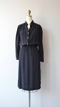 Vintage 1970s jet black silk shirtwaist dress with white buttons, collarless neckline, cuffed sleeves and elastic waist. --- M E A S U R E M E N T S ---  fits like: small/medium bust: best fit up to 39 waist: 24-31 hip: 40 length: 48 brand/maker: Carole Little condition: excellent  to ensure a good fit, please read the sizing guide: http://www.etsy.com/shop/DearGolden/policy  ✩ layaway is available for this item  ✩ more vintage dresses ✩ http://www...