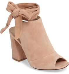 Soft suede and a high vamp define this cool-weather transition bootie outfitted with a squared peep toe and wraparound straps that tie above the ankle.