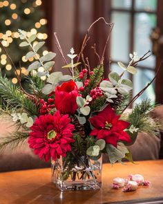 """{$tab:description} Add the perfectholiday accent Red gerbera daisy, tulip, and mini poinsettia mingle with winter greenery, cones, and birch twigs in a 4"""" glass cube vase of our clear acrylic water. It's a lovely silk flower bouquet of holiday happiness. {$tab:DETAILS}  18"""" Height x 18"""" Width Glass Cube Vase - 4'H x 4""""W x 4""""L Fresh Holiday Happiness Arrives Fully Shaped & Ready to Display Designed and Assembled in the USA PetalsExclusive  {$tab:SHIPPING & RETURNS} S..."""