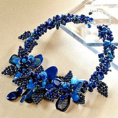 Want it! - by designer Nakamol weaves pieces of lapis in varying sizes and shapes from 3mm round to 20mm oval with glass and dyed agate beads from 12mm to 25mm. The result, an organic masterpiece of flower and leaf shapes. Strung on silver-plated wires with lobster claw clasp.
