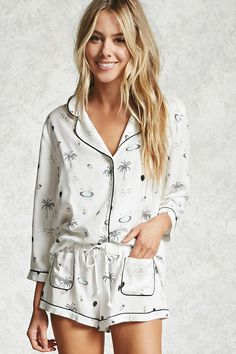 A PJ set featuring a woven shirt with assorted cat, balloon, palm tree, and light bulb graphics, contrast piping, a notched collar, button front, and long sleeves, as well as a pair of woven shorts featuring the same graphics, contrast piping, a drawstring elasticized waist, and two front patch pockets.