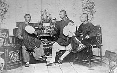 Posed: This image shows three young Chinese men sitting in their home in the late 1860s. A...