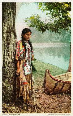 Young Native American girl standing by a lake in this vintage postcard
