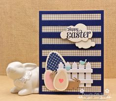 handmade Easter card from Empty Nest Crafter ... die cuts ... navy stripes over kraft gingham ... die cut white picket fence, eggs, bunnies and birds ... luv how the sentiment is stamped on die cut clouds with faux stiched embossed borders ...