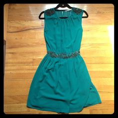 Zara Trafaluc Teal Dress with Sparkle Accents I wish I could wear this Zara Trafaluc dress forever but I grew out of it! You can wear it any time of year, given it's combined color and style. Can fit XS to a smaller medium, as the waistline allows for some stretching while still offering a figure. Sparkle accents are found on the shoulders and waist of the dress. The waistline is cinched for a slimming effect, and a sexy but not revealing slit in the upper back is attracted by a button…