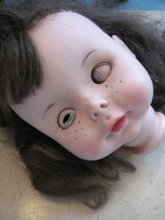 Creepy doll head with rotting eyes. From rudysroundup