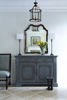 Wedgewood Blue Distressed Look Dresser, White lamps, Dark framed mirror and a byzantine chandelier, blue & white chair .. all in perfect balance.
