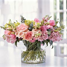 Spiral-stemmed arrangement with snapdragons, roses, tulips, lisianthus, eucalyptus, and viburnum.