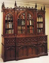 A Regency period mahogany Gothic breakfront bookcase after a design by George Smith (A Collection of Designs for Household Furniture, 1808, plate 103). This magnificent neo-gothic antique bookcase contains a full size desk within the central case section, complete with numerous secret compartments.