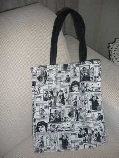 Bolsa em tecido decorativo de Histórias em Quadrinhos (HQ), forrada em preto, com bolso interno e alças de lona também na cor preta. R$45,00