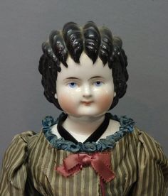 China head doll with black hair in the 'spill curl' style, c. 1870's.