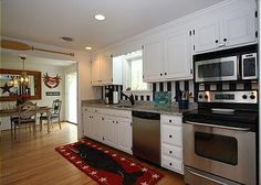 Striped kitchen wall with white cabinets and stainless steel appliances