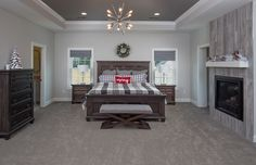 This luxurious grey carpet with a subtle pattern works great in a master bedroom.    Master Bedroom Carpet: Tuftex Pacific Ridge, Color: Stone Age Fireplace Tile: Florida Tile Relive 8x48, Color: Alaska     J.E. Evans Photography