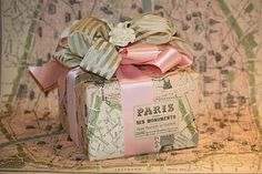 map wrap with pink and green bows. This would be wonderful if you were planning a surprise trip somewhere for someone - give them the tickets wrapped like this!