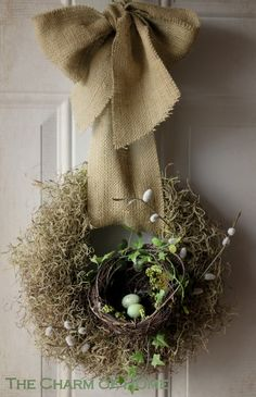 A Spring wreath made of spanish moss, pussy willows and a bird nest  A burlap bow is added for hanging.