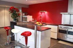 cuisine blanche à mur rouge et plan de travail en quartz noir // ilot central avec espace bar surélevé // grand piano de cuisson avec hotte