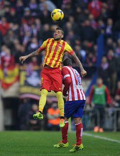 Daniel Alves (L) of FC Barcelona heads the ball ahead of Jorge Resurreccion 'Koke' of Club Atletico de Madrid during the La Liga match between Club Atletico de Madrid and FC Barcelona at Vicente Calderon Stadium on January 11, 2014 in Madrid, Spain.