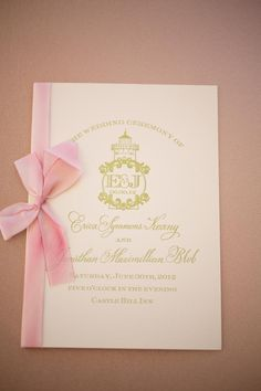 Erica and Jonathan's wedding ceremony program featured a lighthouse-themed monogram in gold and was tied with a pink ribbon. #weddingprogram Photography: Carrie Rodman Photography. Read More: http://www.insideweddings.com/weddings/new-england-summer-wedding-by-the-seashore/429/