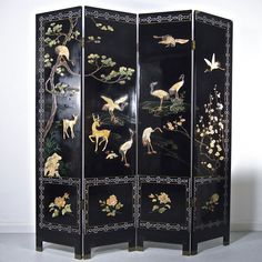 A large Chinese black lacquered four fold panel screen, 20th century. A large Chinese black lacquered four fold panel screen, 20th century. Of rectangular form, with jade and hardstone inlaid decorated to the upper sections depicting cranes and deer in a landscape setting with further painted details and gilt highlights, the four square panels beneath inlaid with chrysanthemums and roses. The reverse in further decorated with gilt painted cranes amongst clouds. 72 in (182.9 cm) height, 64 in…