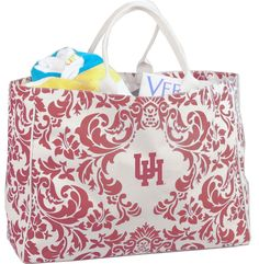 Thick canvas and soft reinforced handles with piping trim give this large tote the perfect look and feel. Great for spring time fun or toting to class. Features the overall damask print and the collegiate logo.