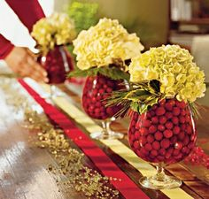I love the cranberry filled brandy snifter with hydrangea, holly, and pine.  Lovely centerpiece option for a narrow table.