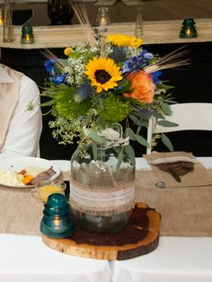 """Moonshine"" jug centerpiece.  With sunflowers, roses, blue delphinium, queen Anne's lace, green tricks, wheat and seeded eucalyptus. Flowers  by Bloom and Leaf Event Florist  Austin, TX.  Photo by Tim  Malkemus Photography."