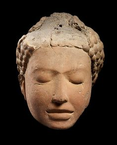 9th C. The Buddha in meditation was a favored subject in Mon art. Dvaravati style;  is joined eyebrow, full lower lip, and bulbous curls. central Thailand. terracotta.